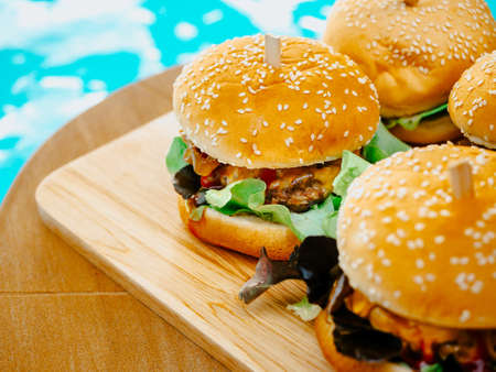 Delicious fresh homemade burger set. Closeup tasty homemade hamburgers on wooden tray or wood cutting board on dark background near the swimming pool.