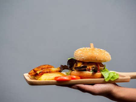 Delicious fresh homemade burger set. hand holding and showing tasty homemade hamburger with french fries and sliced tomatoes on wooden tray or wood cutting board with copy space. 스톡 콘텐츠