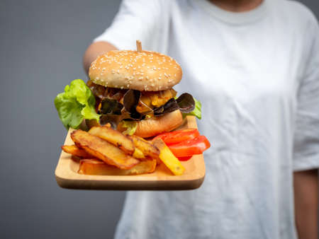 Delicious fresh homemade burger set. Woman wearing casual white t-shirt holding and showing tasty homemade hamburger with french fries and sliced tomatoes on wooden tray or wood cutting board.