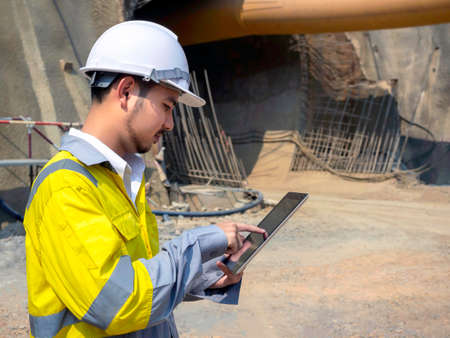 Young handsome Asian tunnel engineering wearing high visibility jacket and white safety helmet working and using digital tablet at tunnel construction site area.