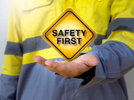 """Work safety concept. Word """"Safety first"""" sign and aid symbol on square yellow sign on hand of engineering people wearing yellow high visibility jacket. Banque d'images"""