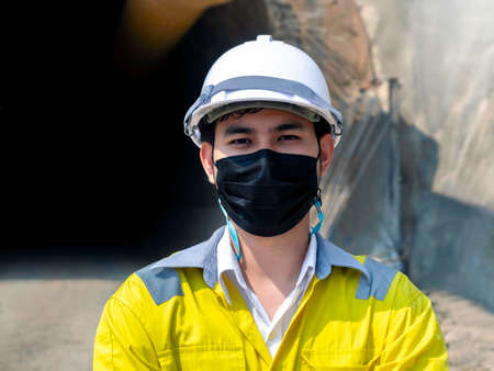 Portrait of young Asian tunnel engineering wearing high visibility jacket, face mask and white safety helmet standing with arms folded in front of the railway tunnel construction site background. 스톡 콘텐츠