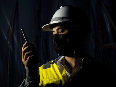 Young Asian engineering man wearing yellow high visibility safety jacket, face mask and white safety helmet or hard hat using walkie talkie in dark railway tunnel construction site area background.