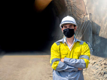 Portrait of young Asian tunnel engineering wearing high visibility jacket, face mask and white safety helmet standing with arms folded on railway tunnel construction site background with copy space.