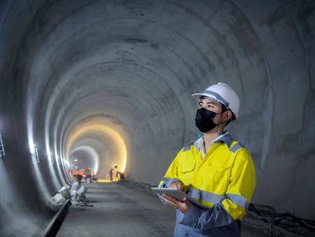 Young Asian tunnel engineering wearing high visibility jacket, face mask and white safety helmet working and using digital tablet in dark railway tunnel construction site area with copy space.