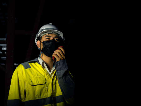 Young Asian engineering man wearing yellow high visibility safety jacket, face mask and white safety helmet or hard hat using walkie talkie in dark railway tunnel construction site with copy space.