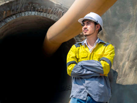 Portrait of young Asian tunnel engineering wearing yellow high visibility jacket and white safety helmet standing with arms folded in front of the railway tunnel construction site with copy space.