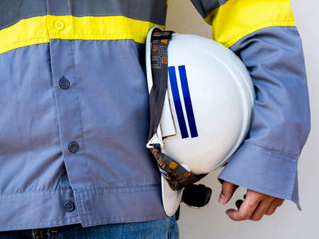 Engineering people wearing yellow high visibility safety jacket holding white safety helmet or hard hat isolated on white background. 스톡 콘텐츠