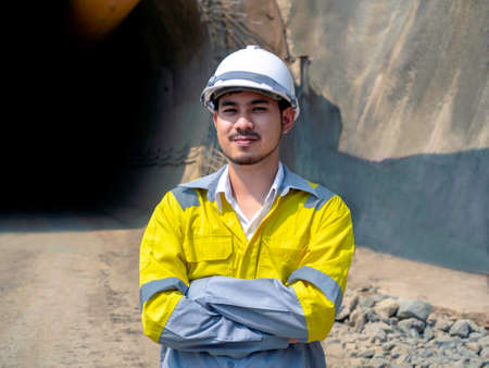 Portrait of young handsome Asian tunnel engineering wearing yellow high visibility jacket and white safety helmet standing with arms folded in front of the railway tunnel construction site area.