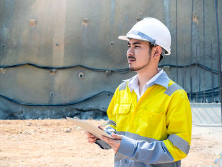 Young handsome Asian tunnel engineering wearing high visibility jacket and white safety helmet working and using digital tablet at tunnel construction site area with copy space.