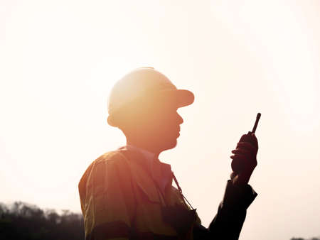 Silhouette side view of young Asian engineering man wearing yellow high visibility safety jacket and white safety helmet or hard hat using walkie talkie on sunset background.