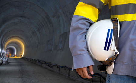 Engineering people wearing yellow high visibility safety jacket holding white safety helmet or hard hat on dark railway tunnel construction site background with copy space. 스톡 콘텐츠