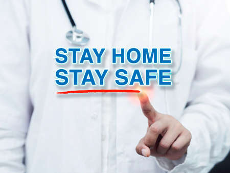 Message STAY HOME STAY SAFE and red underline stroke writing by doctor's finger in a white coat and medical stethoscope. Stay safe, self-protection, self quarantine and social disdancing concept.