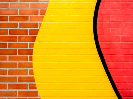 Brick wall background with yellow and red painted.Empty space on vivid color brick wall texture.