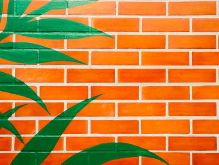 Brick wall background with green leaves painted.Empty space on vivid color brick wall texture.