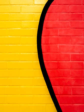 Yellow and red painted brick wall background.Empty space on vivid color brick wall texture, vertical style.