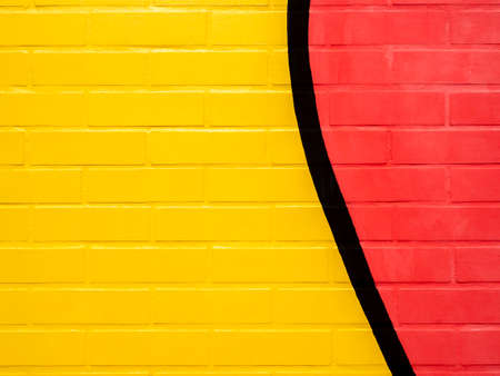 Yellow and red painted brick wall background.Empty space on vivid color brick wall texture.