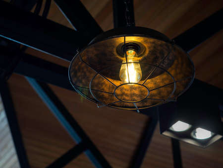 Vintage metal frame pendant lamp. Close-up of shining electric ceiling light with bulb decoration hanging from the ceiling in the dark. Stockfoto