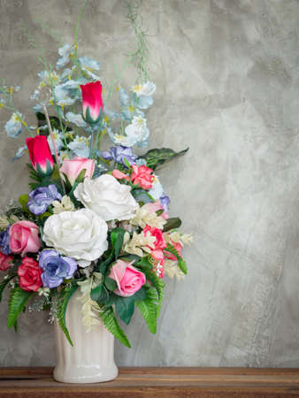 Beautiful colorful bouquet flowers in the white vintage vase decoration on wooden table on loft-style concrete wall background with copy space, vertical style.