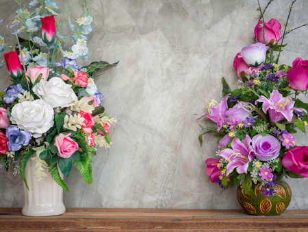 Beautiful colorful bouquet flowers in the vintage vase decoration on wooden table on loft-style concrete wall background with copy space.