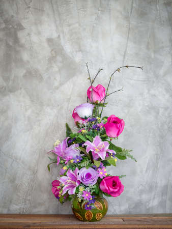 Beautiful colorful bouquet flowers in the vintage vase decoration on wooden table on loft-style concrete wall background with copy space, vertical style. Stockfoto