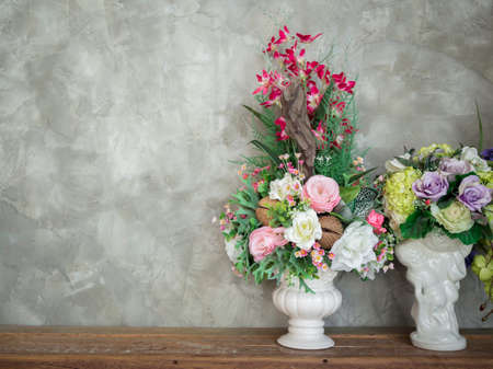Beautiful colorful bouquet flowers in the white vintage vase decoration on wooden table on loft-style concrete wall background with copy space.