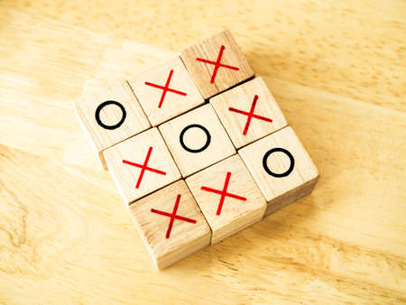 Tic Tac Toe game made of wooden blocks. Top view of wooden OX game on wood table. Business marketing strategy planning concept.