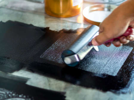 Motion blur of the artist hand, printmaker rolling a printmaking roller with black relief ink color in the art studio, close up. Linocut, woodcut, etching and silkscreen art printing step process. Stockfoto