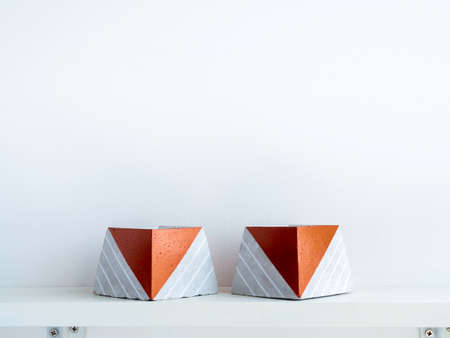 Empty DIY concrete pots, pyramid shape on a white wooden shelf on white wall background with copy space. Two unique copper color painted cement planters. Stockfoto