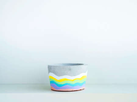 Empty colorful DIY round concrete pot on a white wooden shelf on white wall background with copy space. Unique rainbow color painted cement planter.