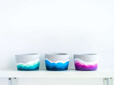 Empty colorful DIY round concrete pots on a white wooden shelf on white wall background with copy space. Three unique colorful color painted cement planters.
