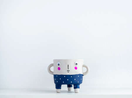 Empty cute face ceramic plant pot with on white wooden shelf isolated on white wall background with copy space. Small modern DIY cement planter trendy decoration.