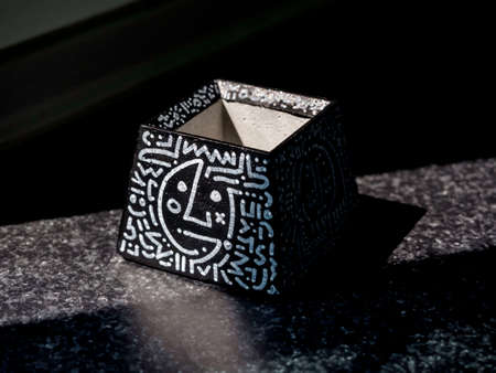 DIY black concrete pot, pyramid shape with art drawing on dark background. Unique color painted cement planter.
