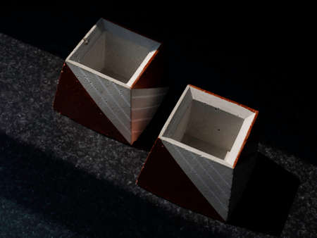 Empty DIY concrete pots, pyramid shape on dark background, top view. Two unique copper color painted cement planters.