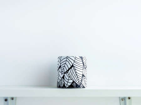 Empty DIY round shape concrete pot with leaves drawing isolated on a white wooden shelf on white wall background with copy space. Unique color painted cement planter.