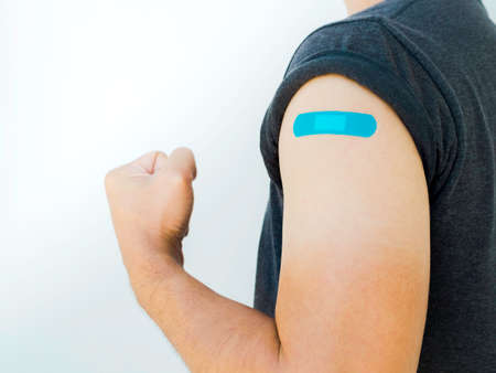 Vaccinations, bandage on vaccinated people concept. Blue bandage on man shoulder who wearing grey shirt and showing strong gesture with fist and arm after vaccination treatment on white background.