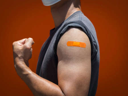 Vaccinations, bandage plaster on vaccinated people's arm concept. Orange color adhesive bandage on the strong man's arm who fist hand and showing muscle after vaccination treatment.