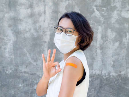 Vaccinations, bandage plaster on vaccinated people's arm concept. Orange color adhesive bandage on business woman's arm who wearing white face mask, showing ok hand sign after vaccination treatment.