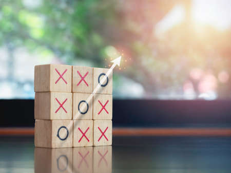 Shiny transparent white success arrow rising on the circle icon on tic tac toe wooden block game on table on green nature background with copy space. Winner, strategy and business goal concept.