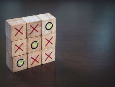 Three winning green check mark icons with red cross on tic tac toe wooden block game, on wood table background with copy space. Winner, strategy and business goal concept. Imagens