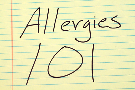 The words Allergies 101 on a yellow legal pad Stock Photo