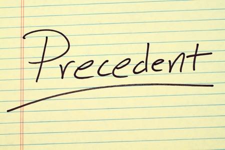 """La parola """"Precedent"""" sottolineata su un blocco legale giallo"""