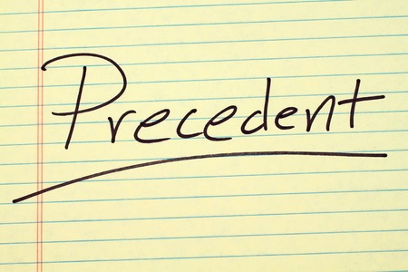 The word Precedent underlined on a yellow legal pad