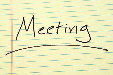 The word Meeting underlined on a yellow legal pad Stock fotó