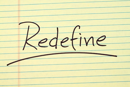 The word Redefine underlined on a yellow legal pad