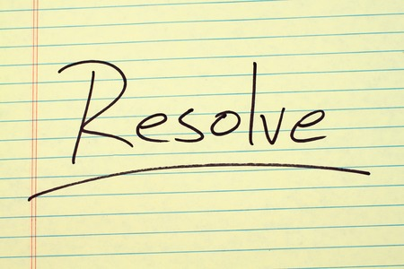 The word Resolve underlined on a yellow legal pad