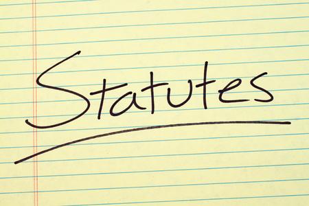 Het woord 'Statuten' is onderstreept op een geel juridisch pad