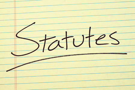The word Statutes underlined on a yellow legal pad