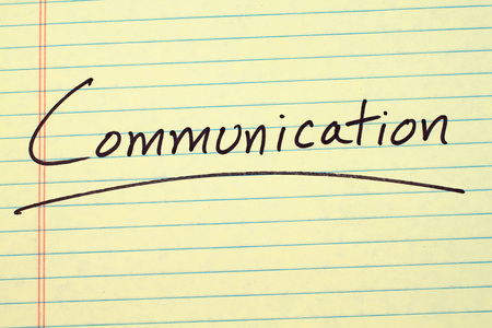 The word Communication underlined on a yellow legal pad
