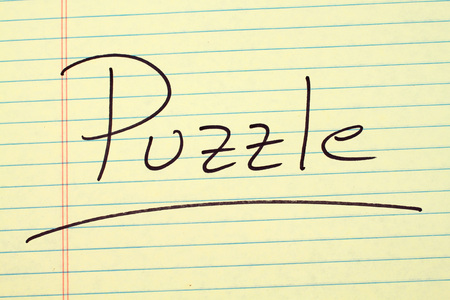The word Puzzle underlined on a yellow legal pad